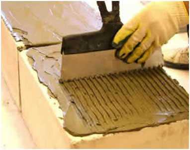 Приготовленный клей при помощи зубчатой кельмы, подбираемой по толщине блока, наносится на горизонтальную и вертикальную поверхности и равномерно наносится слоем 3-5 мм.